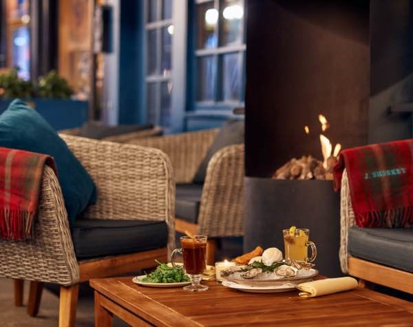 Crackling fire, warm wooden blankets, pillows, some dishes of food on the table ready for nibbling with friends.